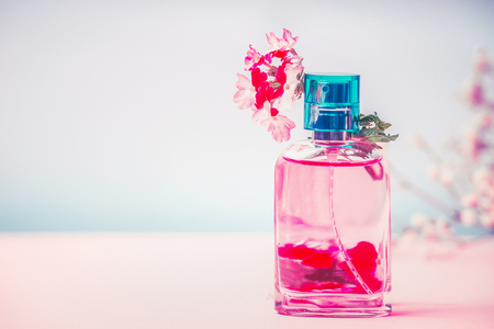 holistic view: Pink Bottle of perfume with flowers, natural cosmetic product or beauty concept on pastel blue background, front view Stock Photo