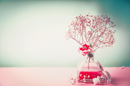 holistic view: Spa , wellness or natural cosmetic still life with bottle of lotion and flowers on pastel color background, front view, banner, beauty  concept