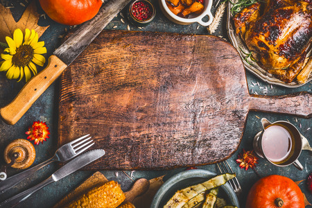 Sfondo cena del Ringraziamento con tacchino, salsa, verdure grigliate, mais, posate, zucca, foglie cadute e composizioni floreali intorno bordo di sventramento in legno, vista dall'alto. Archivio Fotografico