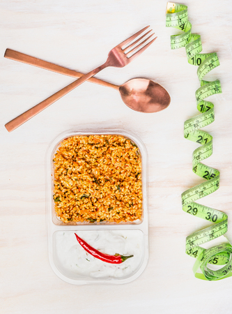 Healthy diet lunch eating  with couscous salad and yogurt. Vegetarian salad lunch box in plastic package with cutlery and Measuring tape on withe wooden background, top view