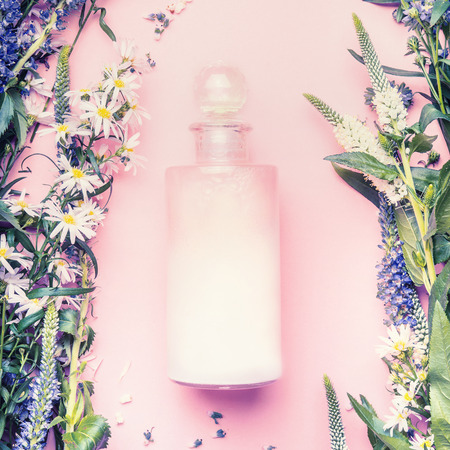 Natural cosmetic product bottle of lotion,shampoo or moisturizer with herbs and flowers on pink background, top view, copy space,  square.  Beauty, skin and hair care concept