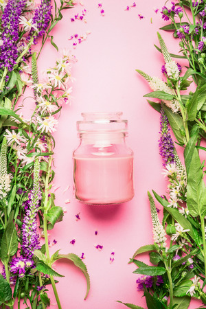 Natural herbal skin care cosmetic concept. Glass jar with cream or lotion and fresh herbs and flowers on pink background, top view, copy space, vertical.  Beauty, skin and hair care concept