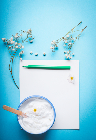 Jar of cream with flowers and spatula on blank paper with pen for Note or list on blue background. Natural herbal skin care cosmetic concept, top view.  Beauty, skin and hair care concept