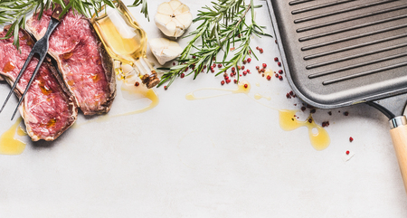 Raw fresh meat Striploin Steak  with ingredients: herbs,spices, oil and frying Grill pan on white stone kitchen table background, top view