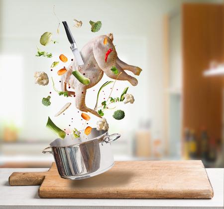 Het vliegen van ruwe kippenvoorraad, bouillon of soepingrediënten met gehele kip, groenten, kruiden, mes en kokende pot bij keukenachtergrond. Vliegend voedselconcept, Gezonde voedingvoedsel. Stockfoto