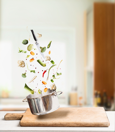Flying cooking ingredients for vegetables stock, broth or soup with pot and knife on table at kitchen background. Healthy vegetarian food concept Stock Photo