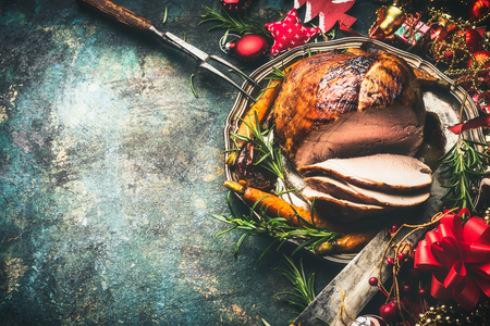Roasted sliced Christmas ham on festive table background with decoration, top view