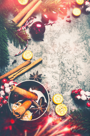Christmas background with mulled wine , spices , festive Christmas decoration and bokeh lighting on rustic vintage background,top view, frame