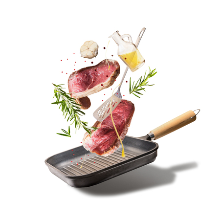 Flying raw beef steaks, with herbs, oil and spices with grill pan and kitchen utensils, isolated on white background, front view. Flying  food concept Stockfoto