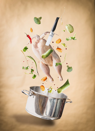 Flying raw chicken stock ,bouillon or soup ingredients with whole chicken, vegetables,seasoning, knife and cooking pot at natural beige background. Flying food concept, Healthy diet food.