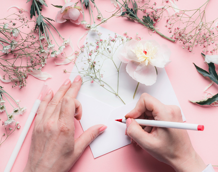 Female Hands write on envelope with flowers on pink tables background.  Wedding, invitation ,Valentine day,  Mothers Day greeting and love concept. Flat lay, top view, copyspace