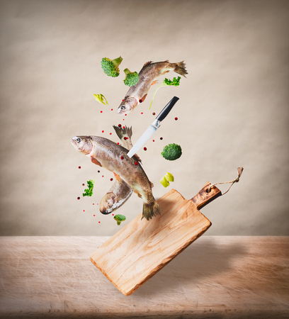 Flying raw whole trout fishes with vegetables, oil and spices ingredients above wooden cutting board for tasty cooking on desk kitchen table at beige background. Healthy food or diet eating  concept. Stok Fotoğraf
