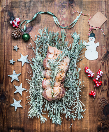 Christmas roast preparation on wooden background with festive decoration, top view