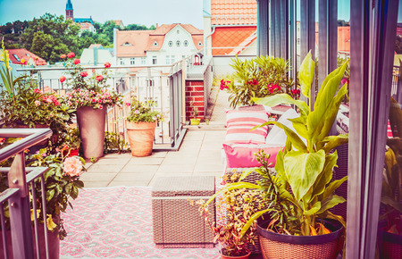 Pretty summer terrace or balcony of  penthouse with flowers patio pots ,  outdoor furniture and nice city view Stock Photo
