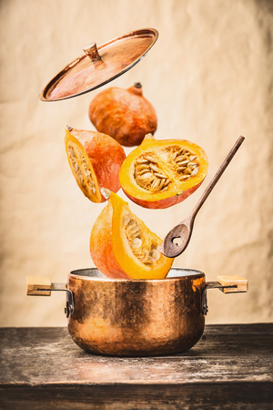 Copper cooking pot with flying pumpkin with knife ,  open lid and wooden spoon on table, at wall background , front view. Autumn seasonal recipes and eating concept
