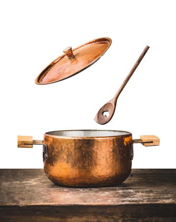 Cobre, cozinhando potenciômetro, com, voando aberto, tampa, e, colher madeira, ligado, tabela, isolado, branco, fundo, vista dianteira Foto de archivo - 83482953