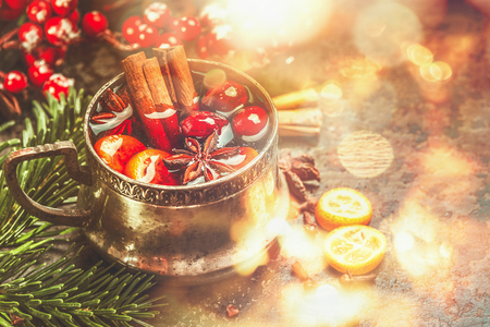Mug of mulled wine with spices at festive Christmas background with bokeh lighting Stock Photo