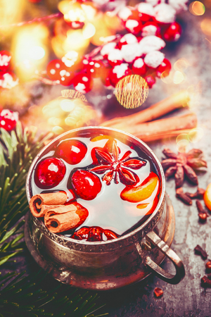 Cup of mulled wine with spices at festive Christmas background with bokeh lighting