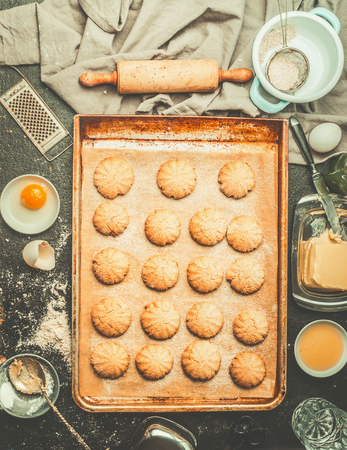 Cookies on baking tray with ingredients and rolling pin, top view