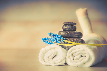 Spa or wellness setting with massage equipment and flowers and herbal balls