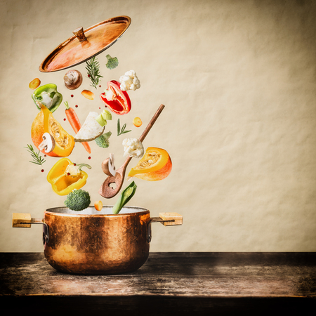 Healthy vegetarian eating and cooking with various flying chopped vegetables ingredients, cooking pot and  spoon at wooden table at natural background, front view. Clean food concept Stockfoto