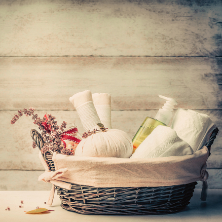 Massage or sauna setting in basket with herbal compress balls , fresh herbs and cosmetic products on wooden background, front view. Healthy Lifestyle or Spa and wellness concept Stock Photo
