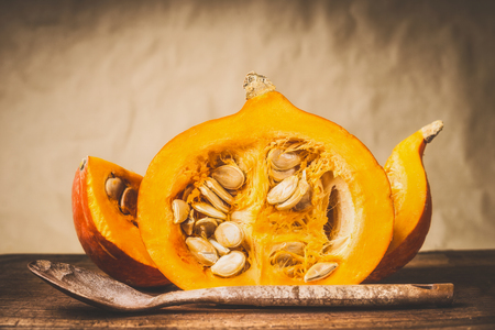 Half pumpkin with seeds and wooden cooking spoon at natural beige background, front view. Healthy autumn seasonal food and eating