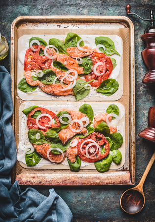 Tarte flambee with salmon , spinach and tomatoes , cooking preparation on rustic kitchen table background, top view Stock Photo
