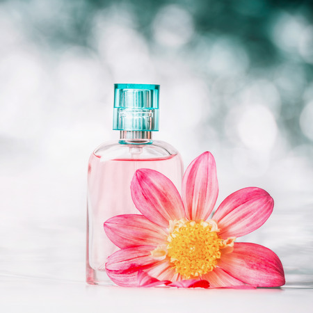 Perfume bottle with pink flower at bokeh background, front view, close up