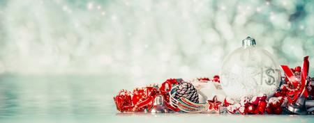 Christmas background with glass balls and red festive decoration at winter bokeh background, front view, banner