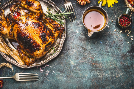 Roasted turkey with sauce served for Thanksgiving dinner on rustic table background, top view