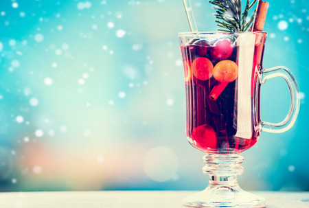 Mulled wine in cup with spices at winter day background with snow, front view, place for text Stock Photo