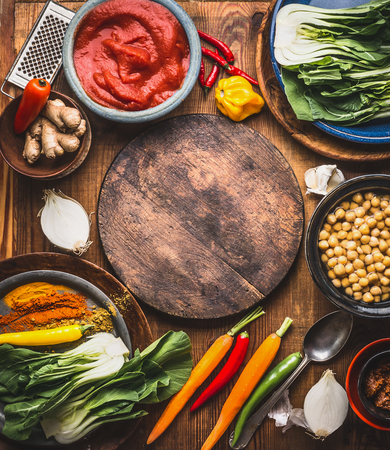 Vegetarian cooking ingredients with chick peas dish, colorful spices, tomatoes paste, ginger and vegetables around wooden cutting board, top view, frame. Healthy eating or Indian cuisine concept Foto de archivo