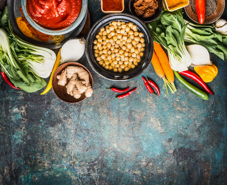 Vegetarian cooking ingredients with chick peas dish, spicy indian curry paste , greens, ginger and vegetables on rustic background, top view, border.  Healthy food and eating or Indian cuisine concept