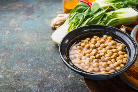 Cooked Chick peas in bowl with vegetarian cooking ingredients on rustic background, place for text, close up.  Healthy food and eating concept Stock Photo