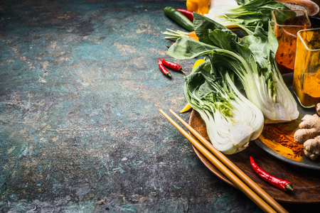 Asian food and eating  concept: Chinese or Thai cuisine, cooking ingredients with pak choi and chopsticks on dark vintage background, place for text Stock Photo