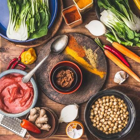 Healthy vegan or vegetarian cooking and eating concept with Chick peas, colorful spices , cooking spoon and ingredients, top view. Indian cuisine