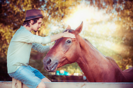 Sentimental scene of communication between man and horse. A young guy with closed eyes hugs  a head of beautiful red horse Фото со стока