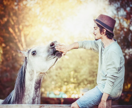 Nice communication between a young man and a horse , guy stretches his hand to the horses mouth, the horse touches his hand with his lips Stock Photo