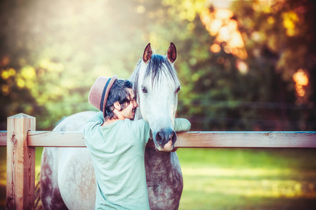 A touching embrace of a young man with hat and a gray horse