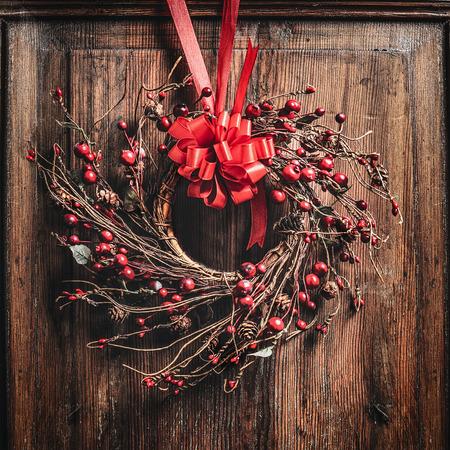 corona de navidad con cinta roja y bayas en madera Foto de archivo
