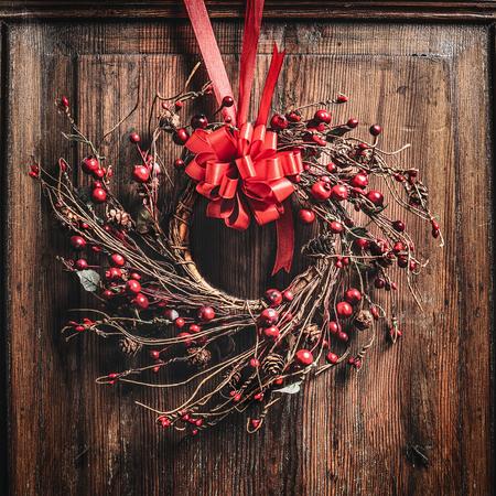 corona de navidad con cinta roja y bayas en madera