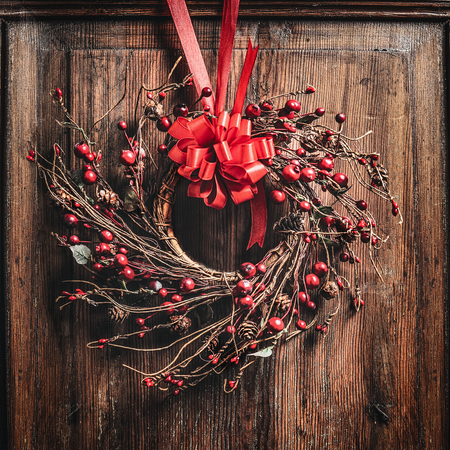 Christmas wreath with red ribbon and berries on wooden Archivio Fotografico