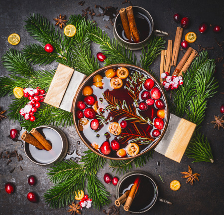 Tasty mulled wine pot with cups and ingredients, top view