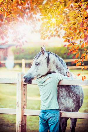 A horse hugs with neck a young guy at autumn country nature background Stok Fotoğraf