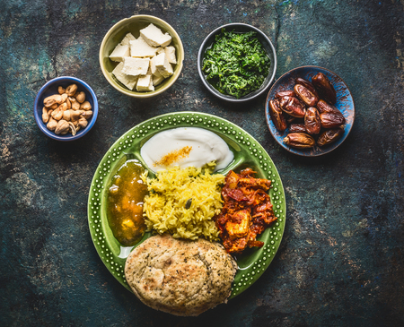 Various indian food bowls with curry, yogurt ,rice,bread ,chutney, paneer cheese and spices on dark rustic background, top view
