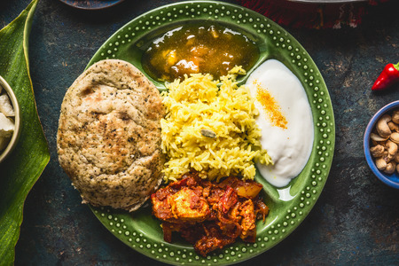 Indian food bowl with curry, yogurt ,rice,bread , chicken,chutney and spices , top view