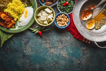 Various indian food bowls with curry, yogurt ,rice,bread , chicken,chutney, paneer cheese and spices on dark rustic background, top view, border