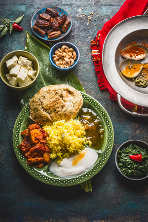 Assorted indian food. Bowls with paneer cheese , curries, rice, naan bread, samosas, chicken,chutney and spices on dark rustic background, top view Stock Photo