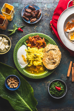 Indian food dish with paneer cheese , curries, rice, naan bread, samosas on dark rustic background, top view Stock Photo - 86947185